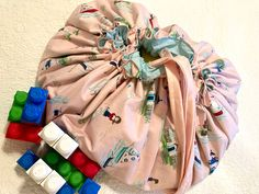Whimsical seaside themed drawstring toy bag that converts to large play mat for fun at home or on the go!| Lighthouses and sailboats in the perfect blend of aqua, pink and red make this play mat delightful| Combine this with their favorite toy inside for the perfect gift(that parents will love too!). Birthday Gifts For Girls, Girl Birthday, Colored Pencil Holder, Twistable Crayons, Crayon Roll, Toddler Girl Gifts, Crayon Holder, Paisley Fabric, Fabric Remnants