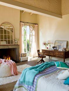 Dormitorio con ventanales de vidrieras en arco, chimenea y tocador rústico. Con tocador