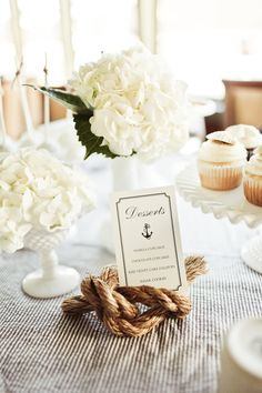 Wedding Theme Inspiration: Nautical. Here's a nautical look, exuding quiet elegance, for those who are fans of white, navy and brown. Pinstriped table cloth, with cream floral centrepieces and a clever table or place card holder made from a knotted rope!♥ Jess