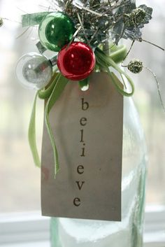 "I used a tea stain tag, stamped with the word ""believe"" finished with a ribbon, vintage tinsel and ornaments to give that vintage look to a new bottle for the holidays."