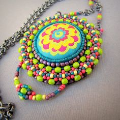 The Flowering Button Mandala Pendant by LaBella Joya. Love the wild colours!