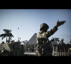 Egyptian army soldiers take position in front of the Great Pyramids of Giza
