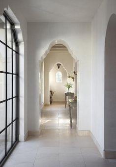 Long hallway features arched doorways filled with gray French console tables.