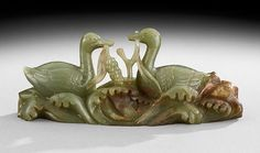 """Chinese Jade Carving, 20th century, the stone of a dark celadon green color depicting a pair of geese with branches of foliage on a wavy ground, l. 9-3/4""""."""