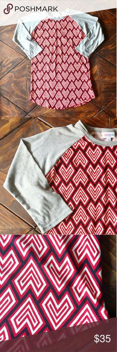 NWT Lularoe Randy Tee Shirt Brand new with tags Randy Tee from Lularoe. Heather grey sleeves with contrasting red, navy blue and white heart patterned bodice. Three quarter sleeves.These tees are extremely soft and comfortable and look great on everyone. Size small! Bundle to save! LuLaRoe Tops Tees - Long Sleeve