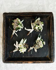 A pin of wax flowers, seeded eucalyptus, and olive leaves accessorized the groomsmen's lapels.