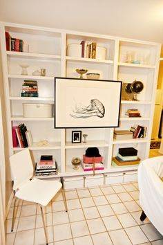 using a print on a bookshelf to cover storage.. i like the white white parson sized bookshelf that isn't crowded