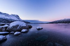 Beautiful photo of the shore of Narvik Fjord surrounded by the snow covered peaks of Norway. The photo was taken midday in December when the sun tries to make it above the horizon but never quite makes it.