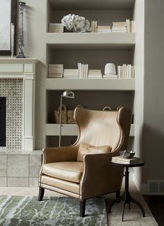 Henry Walker Crestpointe Model Home. Interior Design by Alice Lane Home Collection.   (bookshelves, fireplace, wingback chair, task light, reading light, side table, leather chair)