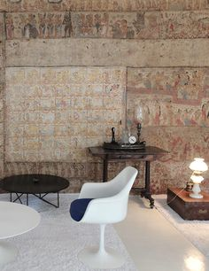 a modern table & tulip chair stand out against  ancient wall art in the home of architect Geoffrey Bawa,