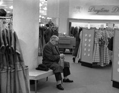 At Gimbels, this gentleman sits out his wife's foray into the dress racks.