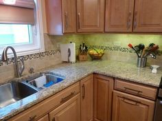 Maple cabinets and love the backsplash and Giallo Ornamental granite countertops.
