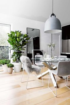 A Nordic dining room with a large pendant light and white metal chairs