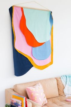Add a big splash of color to your walls with our tutorial for a Colorful DIY Fabric Wall Hanging. The supplies are really inexpensive, and it will definitely make a statement in your home decor. Switch up the colors to fit your personal style! #walldecor #art #diy #modern #interiordecor #wallhanging