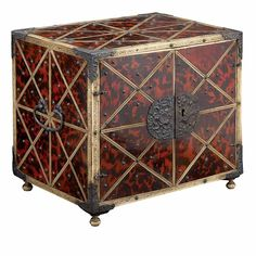 Indo-Portuguese Silver Mounted Stained Tortoise Shell and Ivory Table Cabinet  17th/18th Century  Of rectangular form, with studded diaper veneers and a pair of cupboard doors opening to reveal an interior fitted with six small drawers carved with foliate scrolls, on bun feet.