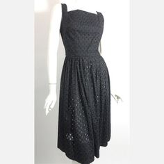 Dorothea's Closet offers up a colorful collection of vintage women's fashions bursting with attention-grabbing patterns, sleek silhouettes and flirty details. A peekaboo eyelet skirt make this little black number a little racier without flaunting too much curve or too much cleavage. A classic fitted bodice and full skirt keep the balance of sweet and sexy.