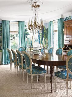 Askins intentionally dropped the height of the chair rail in this dining room decorated by Columbia, South Carolina, designer Karen Minge to accommodate a Zuber wallcovering. Her vibrant pops of turquoise add punch to the oval dining chair backs, which take their cues from Askins's elliptical ceiling above.