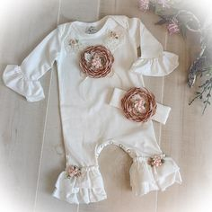 Welcome your little one home in this adorable ruffle romper. The romper features Ivory sequin and beaded lace trim and a fabulous mocha satin flower. Such a unique outfit for your special little lady. Perfect for those first photos.  The optional headband completes the outfit.  Each of these adorable rompers is lovingly hand made for your special little girl. Made from 95% cotton 5% spandex this romper is so soft in addition to being beautiful. Perfect for that first picture or special…