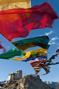 A prayer flag is a colorful rectangular cloth, often found strung along mountain ridges and peaks high in the Himalayas, used to bless the surrounding countryside. Prayer flags come in blue, white, red, green, and yellow; representing the five elements. The flags do not carry prayers to gods, which is a common misconception; rather, the Tibetans believe the prayers and mantras will be blown by the wind to spread the goodwill, peace, wisdom, strength and compassion into all pervading space.