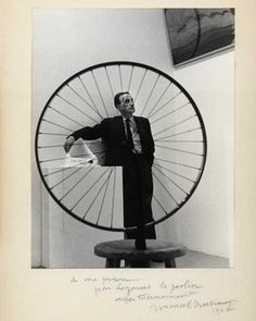 """Marcel Duchamp photo Marvin Lazarus (1918–1982)  1962. Taken at the Museum of Modern Art on the final day of the """"The Art of Assemblage"""" exhibition in 1961. The exhibition included thirteen of Duchamp's works. Lazarus's image captures Duchamp with his artwork: he stands framed within the spokes of his Bicycle Wheel, gazing up at his last painting, Tu m', with one arm familiarly tossed around the shoulder of his Fountain."""