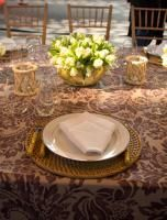 Aerin Lauder designed a table for Kravet that showcased her yet-to-be-released fabric collection for Lee Jofa, covering the table and surrounding walls in a purple damask-patterned linen. The table settings included rattan chargers and bamboo flatware.