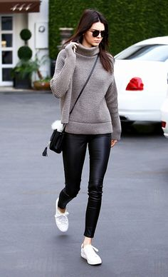 Kendall Jenner wears a ribbed turtleneck, leather leggings, white sneakers, a mini bucket bag, and round sunglasses