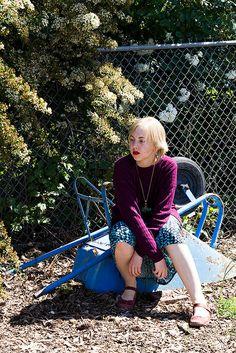 plum purple sweater, perched on an overturned blue wheelbarrow