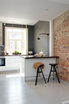White & Grey Memories: 50m2 en dos nivells. Painted grey floorboards, exposed-brick feature wall, grey walls, white gloss handless kitchen. Love this (minus dark worktops).