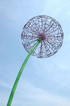 Giant flower made of bike rims. Cleveland Ohio. A 35-ft. tall sculptural dandelion puffball of sorts. Made of old bicycle wheel rims and lit by LEDS, the 2010 eye-catcher is by artist Jake Beckman.