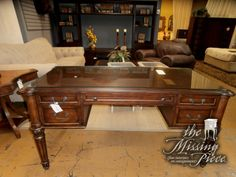 Clean lined writing desk from Ethan Allen. Protective glass top makes it a keeper for years to come. Measures 61*32*32.