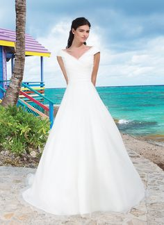 Organza A-line gown features asymmetrical pleated portrait neckline and  bodice. Gown is finished with chapel length train and organza buttons  cover back zipper.