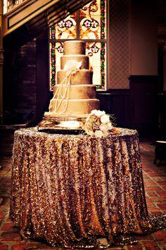 Trouver du matériel glitter qui est beau en fushia, teal, turquoise, émeraude ou silver. Trouver une moyenne table ronde et faire faire une nappe qui touche le sol pour pouvoir mettre le gâteau dessus .  En dessous du gâteau un napperon rond de plume de paon ainsi que des faux diamants d'acrylic entourant celui ci comme confetti