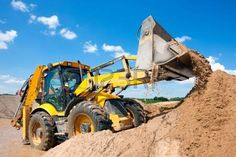 digger: Excavator machine unloading sand with water during earth moving works at construction site