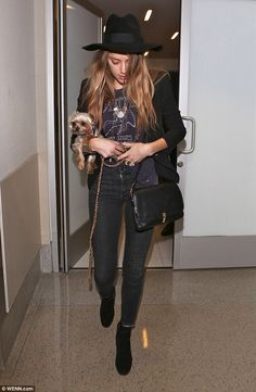 Amber Heard wearing a a large diamond ring on her wedding finger, departs Los Angeles International Airport (LAX) wearing a wide floppy brimmed hat and carrying her pet Yorkshire Terrier
