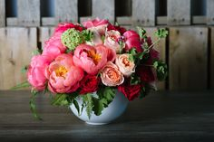 Decadent 'coral charm' peonies are tucked into a bed of ruffled peach and magenta garden roses: 'Peony Fête' by Winston Flowers.
