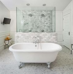 A vintage claw foot bathtub and tub filler stands atop a marble herringbone floor lining a shower wall.