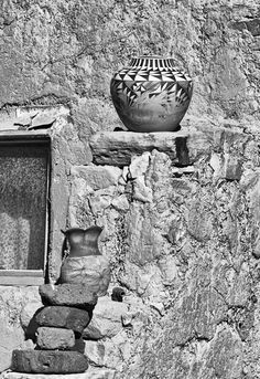 A piece of pottery created by a member of the Acoma Tribe in New Mexico decorated the top of a wall outside the door of one of the dwellings in this Pueblo village.
