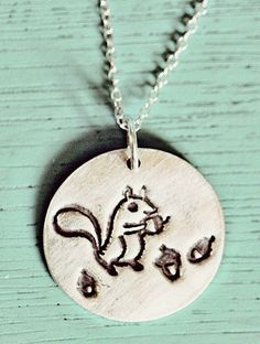 "You will receive this lovingly handmade sterling silver necklace featuring a squirrel happily snacking on acorns. Threaded onto an 18"" fine silver chain this pendant measures approx 3/4"" wide and is m"