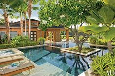 """Tiered swimming pools uniting the main and guest hales, or houses, spill into one another under the dappled shade of a specimen Singapore plumeria. Summit chaises with custom stainless-steel legs rest on an in-pool ledge. """"The proportions and detailing grew out of a desire to harmonize with the surroundings,"""" explains de Reus 