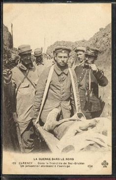 "WW1, Carency, France; A German prisoner carrying a wounded soldier in the ""Sidi…"