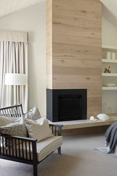Fireplace Design Idea - 6 Different Materials To Use For A Fireplace Surround // A light wood fireplace surround contrasts with the black of the fireplace.