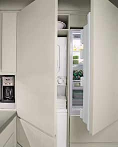"""In the kitchen, one wall houses a refrigerator and washer and dryer behind cabinet doors, as well as a toaster and coffeemaker in an appliance """"garage"""" on a tray that pulls out so you can pour in water."""