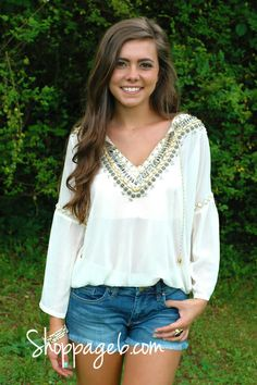 We are obsessed with this top featuring gorgeous beading around the neckline. Features two Gold and White rope and tassels hanging from neckline. Beautiful beading and Gold trimming around the quarter length sleeve. Sheer. Elastic bottom hem. Styled to perfection with lovely Gold accessories and simple clutch. Dress this top up or down with your favorite pair of denim or dressy shorts. This top is the definition of fabulous. Only at Page 6 online.