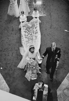 In 1947 Princess Elizabeth married Prince Philip Mountbatten of Greece and Denmark. She ascended to the throne and became Queen Elizabeth II in 1952 upon the death of her father, King George VI.  Her royal wedding gown was designed by Norman Hartnell. It was silk and satin, embroidered with 10,000 seed pearls (imported from the US) crystal beads in garlands of star-shaped lily heads, white York roses with orange blossoms and heads of wheat (symbol of fertility), and a 15' silk tulle train.