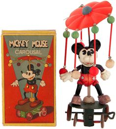 "Original illustrated cardboard box contains toy that measures 7.5"" tall overall w/4.25"" tall celluloid Mickey Mouse figure attached to the wheeled tin base w/built-in key. ""Made In Japan"" as marked on Mickey's back along w/small copyright symbol. Distributed by Geo. Borgfeldt Corp. 1930s"