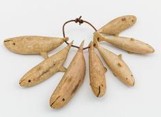 "PENDANT WITH SEVEN WHALES (hunter's amulets)/ Aleut, Aleutian Islands, Alaska, c. 1900, walrus ivory, 3 1/2 x 5 x 3/4"", collection of Jeffrey Myers. Photo by Adam Reich"