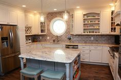 #KitchenRemodel with light colored #cabinets and a unique round window! #kitchen