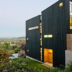 Warm modern High on a hillside in Portland overlooking snowcapped Mt. Hood, a modern house clad in Northwestern wood stands. The architect stained the wood matte black to contrast the natural setting and let the creative window placement shine. Exterior Paint Colors, Exterior Design, Style At Home, Portland House, Downtown Portland, Clapboard Siding, Black Exterior, California Homes, Modern House Design