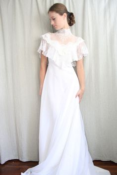 classic white wedding dress from the 1950s. Made with yards and yards of white sheer chiffon, the skirt on this dress is awe-inspiring. So full, and delicate! Delicate sheer lace and tulle at the high neck and behind, with a capelet like faux sleeves covering the shoulders