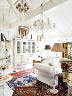 Inside a Famed Costume Designer's Charming Canyon Home | white-washed walls and white furniture with Oriental rugs and a crystal chandelier. very pretty!